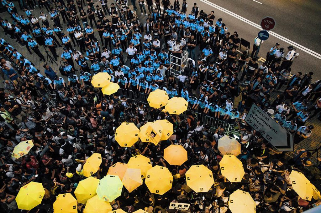 HONG KONG - SEPTEMBER 28: Pro-democracy protesters hold umbrellas in front of police cordon line outside of the Hong Kong Government Complex at Admiratly district on September 28, 2015 in Hong Kong. September 28th marks the one year anniversary of last year's 79-day protest which failed to persuade China to allow a fully democratic vote for the city's next leader in 2017. (Photo by Anthony Kwan/Getty Images)